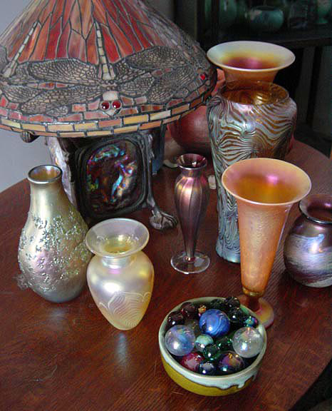 An Art Glass Collection Featuring a Dragonfly Stained Glass Lamp Plus Art Glass Vases and Marbles: : This stained glass lamp is filling double roles in the room. It is useful accent lighting that adds shimmery luminescence to the collection of art glass vases surrounding it. With its colorful stained glass lampshade and graceful form, it also becomes an integral part of the art glass collection. The dragonfly motifs draw the eye to create a focus of interest, while the bronze lamp base adds an interesting counterpoint to all the shimmering glass in the collection.