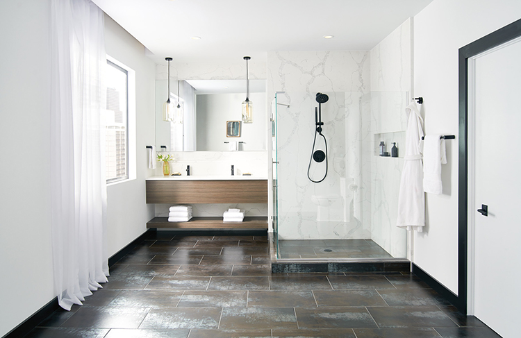 This photo showcases several on-trend bathroom design elements for 2018 including large format tile bathroom flooring; a matte black showerhead and fixtures; a floating vanity with open shelving beneath; and an expansive shower area outfitted with Moen's new shower rails system. Photo courtesy of Moen.com.