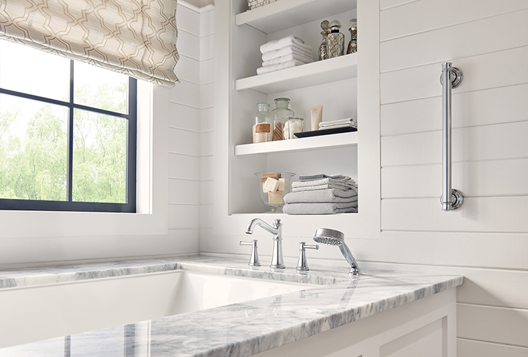 This on-trend transitional bathroom features shiplap wall planks,natural stone surfaces, open shelving, Moen's traditional Belfield bathroom elements, and a convenient grab bar. Photo courtesy of Moen.com.