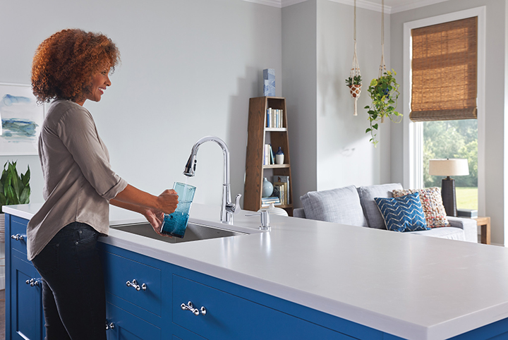 This trendy blue and white kitchen features an open floor plan with a view of the living area. Other on-trend kitchen elements include an undermount sink and a single-lever faucet equipped with Moen's brand new Power Boost™ technology. Photo Courtesy of Moen.com.