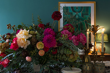 Look past the stunning floral arrangement and still life pictured in the foreground of this photograph; the item of interest in this picture is the wall color behind the arrangement. It's a color by Dunn Edwards known as The Green Hour, and it is that company's selection for 2018 color of the year. Photo courtesy of DunnEdwards.com.