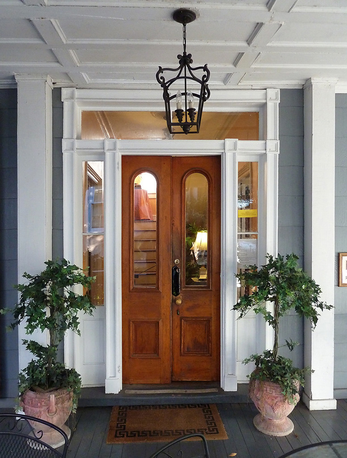 Front entry door of a bed and breakfast decorated with charming potted trees. This symmetrical grouping of plants has a formal elegance that is suitable for traditional, vintage and some transitional style homes. Photo courtesy of Liz West.