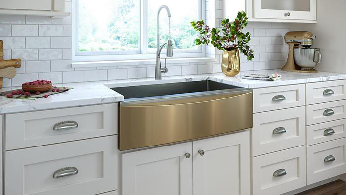 Trendy white kitchen featuring gold and champagne colored accents. The sink is an Elkay Crosstown farmhouse sink with gold front. The champagne colored mixer is by KitchenAid. Photo courtesy of Elkay.com.
