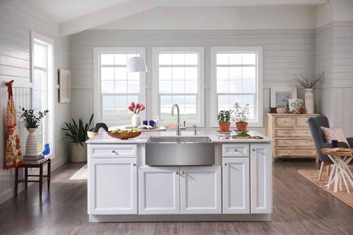 This trendy white kitchen includes a farmhouse sink, wood-finish flooring and a single-lever faucet by Moen. Photo courtesy of Moen.com.