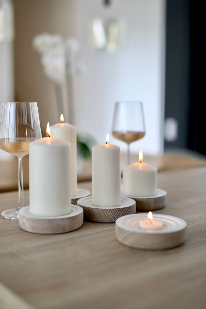 Photo courtesy of Group candles of varying thicknesses and heights together. In this particular design, there are also unifying elements, including the wooden candle holders and the fact that all the candles are the same color.  Photo courtesy of Swabdesign_official - @swabdesign at Unsplash.com.
